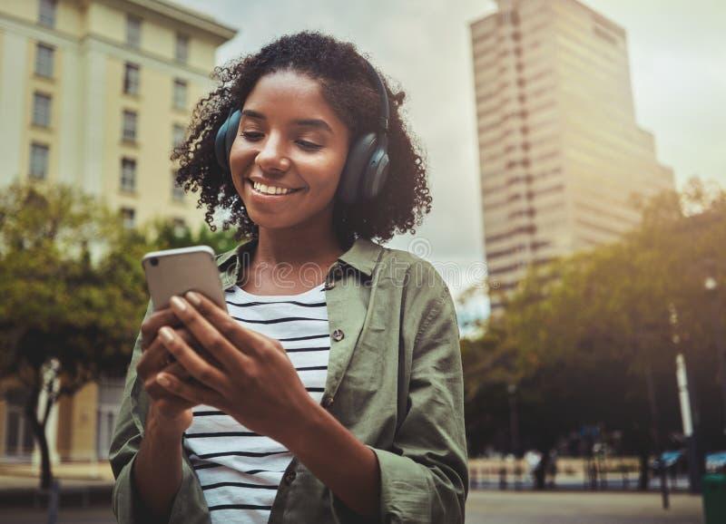 Lycklig flicka som lyssnar till musik som bläddrar det smarta telefoninnehållet arkivbilder