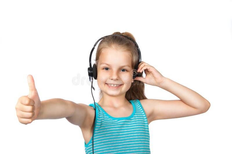 Lycklig flicka som lyssnar till musik på en vit bakgrund royaltyfria foton