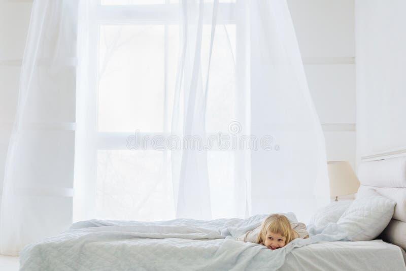 Lycklig flicka som ner ligger på säng i vitt rum med fönstret arkivbild