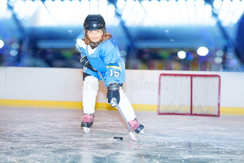 Lycklig flicka som passerar pucken under hockeyleken arkivfoto