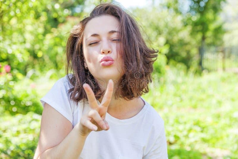 Lycklig flicka som poserar med kyssframsidauttryck Kvinnan för brunetten för skönhetståenden parkerar den unga lyckliga positiva  fotografering för bildbyråer