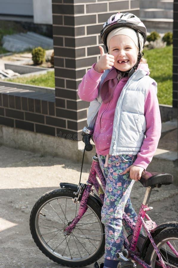 Lycklig flicka som rider en cykel arkivbild