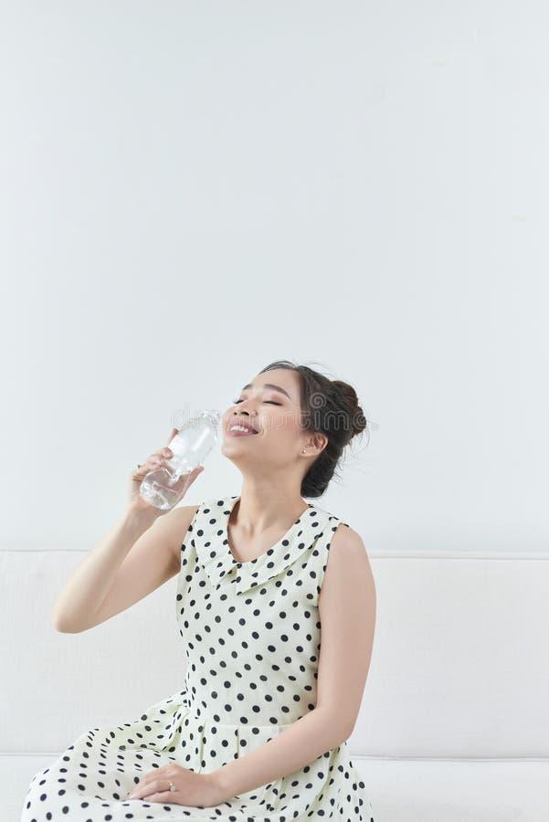 Lycklig flicka som rymmer en vattenflaska som sitter på en soffa i vardagsrummet royaltyfri fotografi