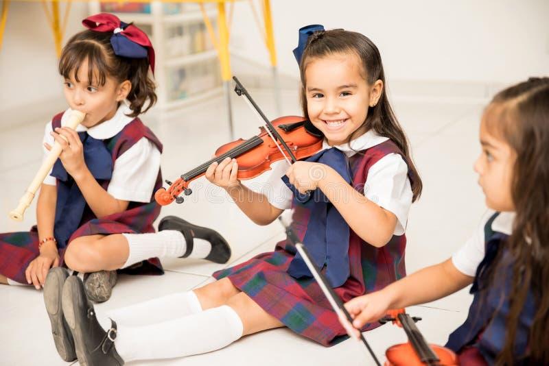 Lycklig flicka som spelar fiolen i förträning arkivfoton