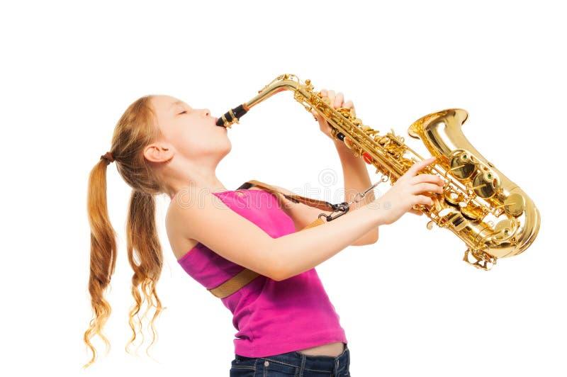 Lycklig flicka som spelar saxofonen på vit bakgrund royaltyfri foto