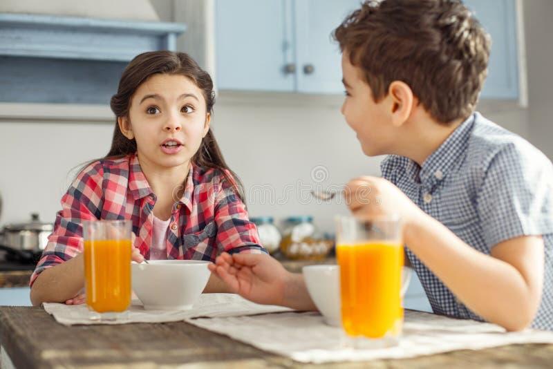 Lycklig flicka som talar med hennes broder och äta royaltyfri bild