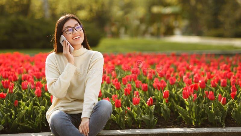 Lycklig flicka som talar på telefonen nära röda tulpan royaltyfri bild