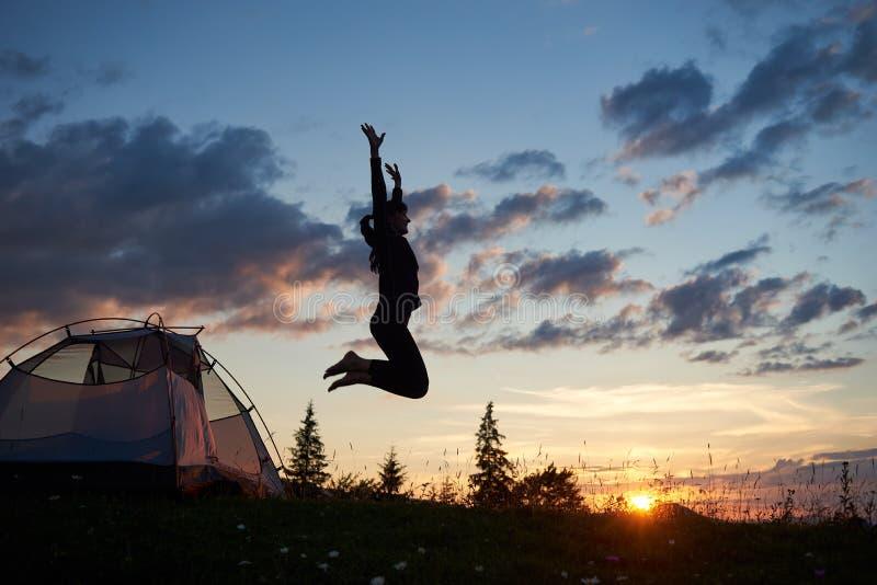 Lycklig flickabanhoppning på gräs med vildblommor på att campa i berg på gryning under blå himmel arkivfoton