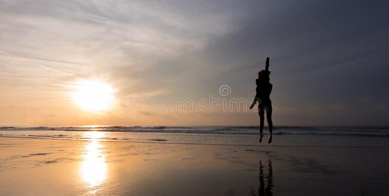 Lycklig flickabanhoppning på stranden framme av solen arkivfoton
