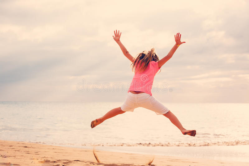 Lycklig flickabanhoppning på stranden på solnedgången royaltyfria foton