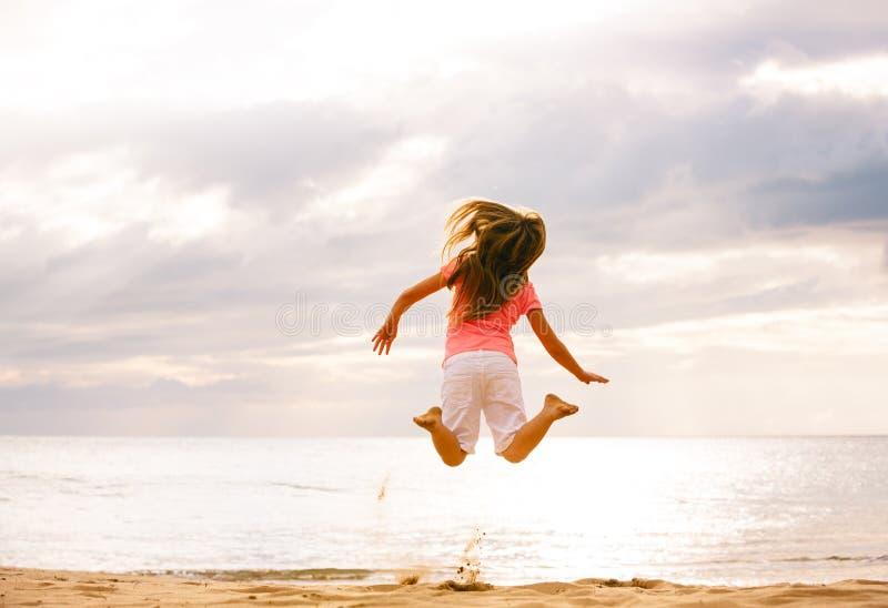 Lycklig flickabanhoppning på stranden på solnedgången royaltyfria bilder
