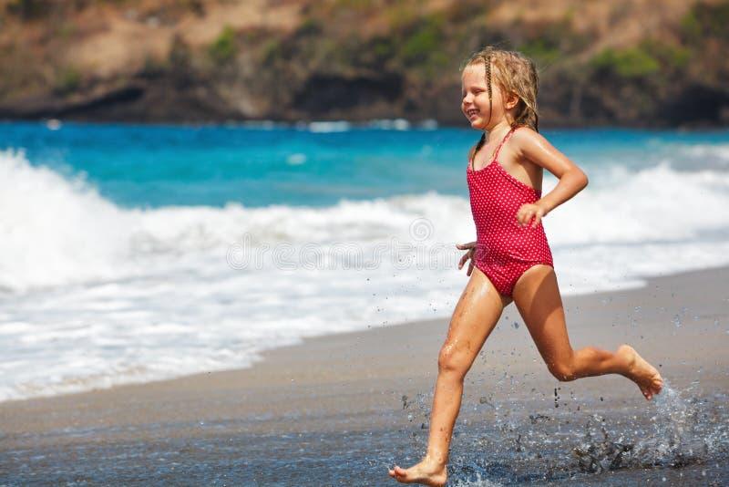 Lycklig flickakörning längs havsbränning vid sandstranden royaltyfria foton
