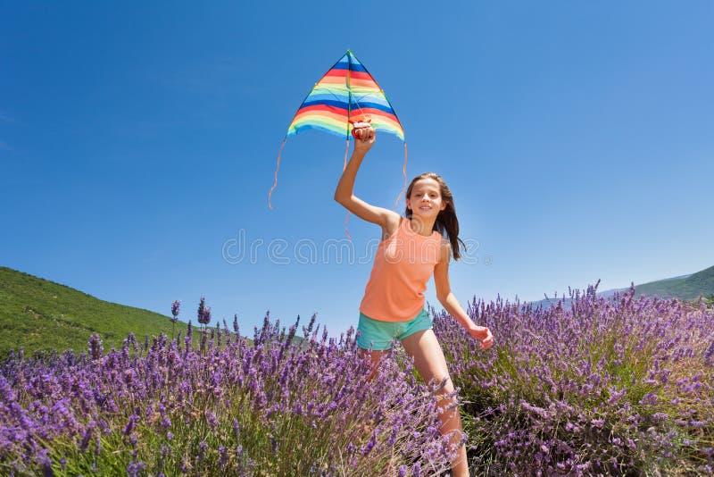 Lycklig flickaspring med draken i lavendelfält royaltyfri bild