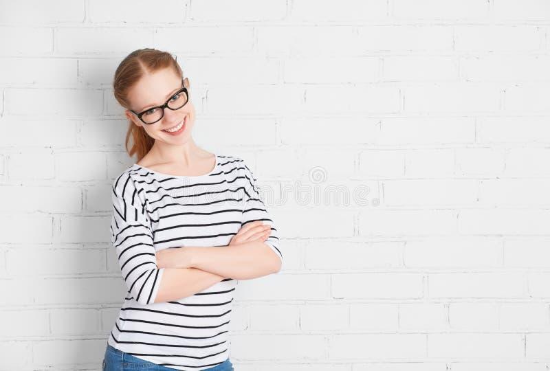 Lycklig flickastudent i exponeringsglas på en tom vit tegelstenvägg arkivbild