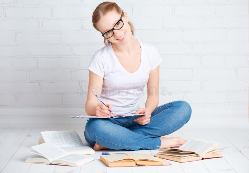Lycklig flickastudent som förbereder läxa som förbereder sig för examenwina arkivbild