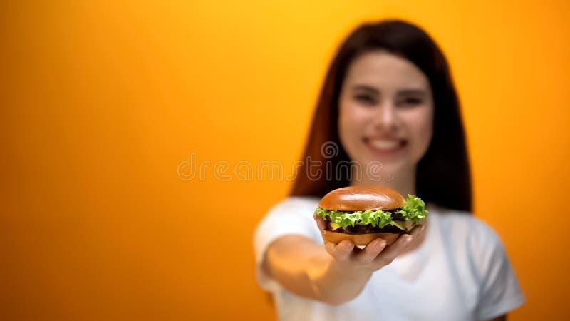 Lycklig flickavisninghamburgare till kameran, tillfredsställd klient av snabbmatrestaurangen royaltyfri fotografi