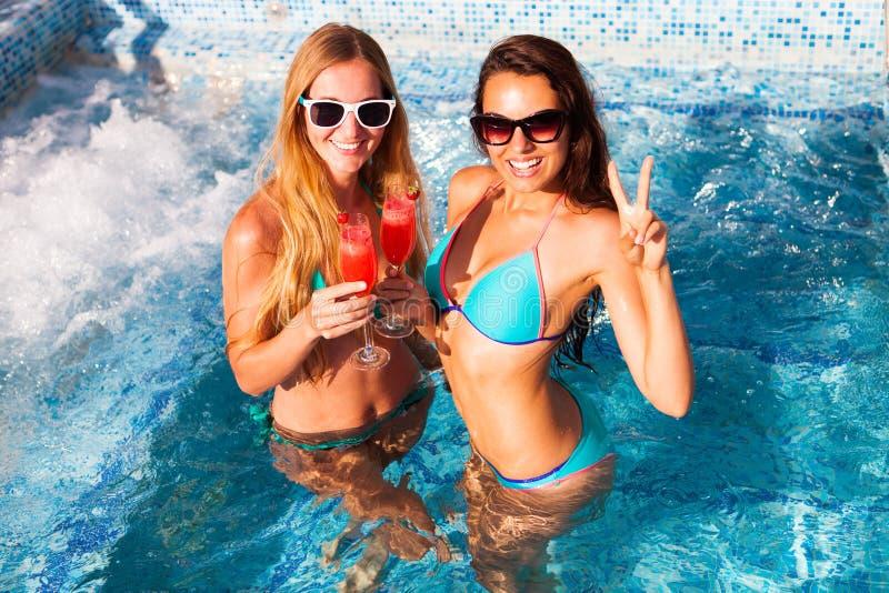Lycklig flickvän med en drink på ett sommarparti vid pölen fotografering för bildbyråer