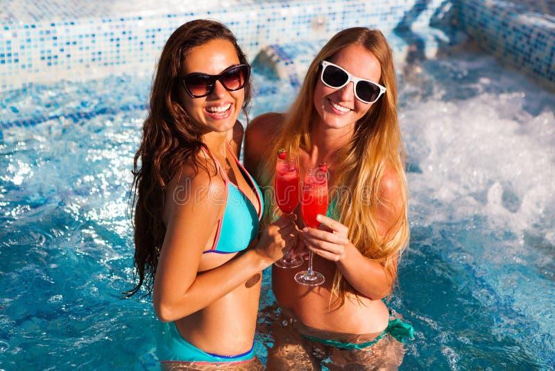 Lycklig flickvän med en drink på ett sommarparti vid pölen arkivfoto