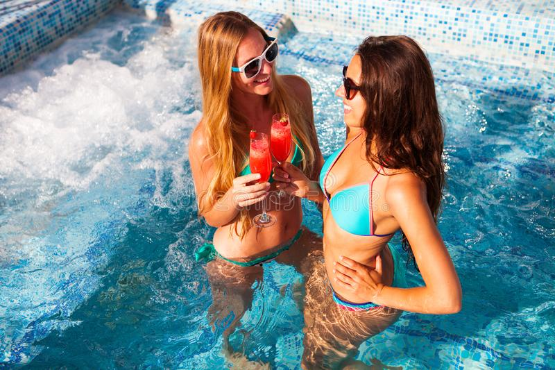 Lycklig flickvän med en drink på ett sommarparti vid pölen royaltyfria foton