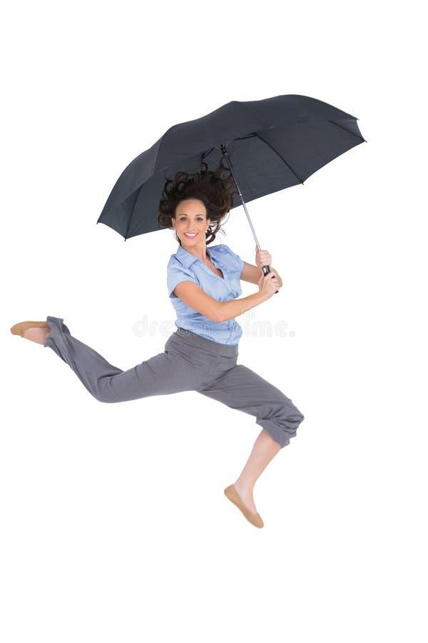 Lycklig flott affärskvinnabanhoppning, medan rymma paraplyet arkivbilder