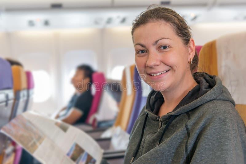 Lycklig flygplanpassagerare med tidskriften i stol som ler under f royaltyfri bild