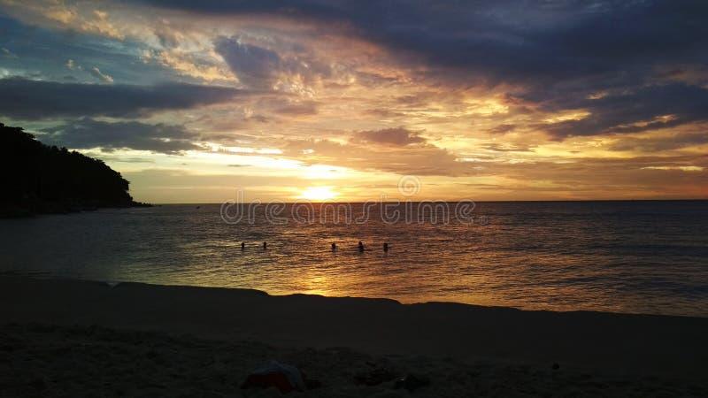 Lycklig folksimning på solnedgången i ferie royaltyfria bilder