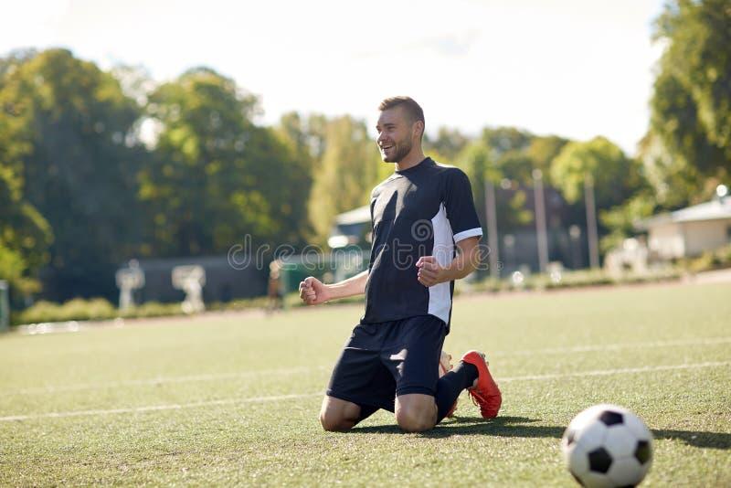 Lycklig fotbollspelare med bollen på fotbollfält arkivfoto
