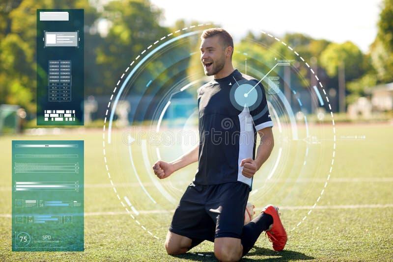 Lycklig fotbollspelare med bollen på fotbollfält arkivbild