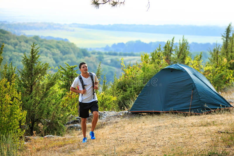 Lycklig fotvandrare för ung man i berg för en sommar royaltyfria foton