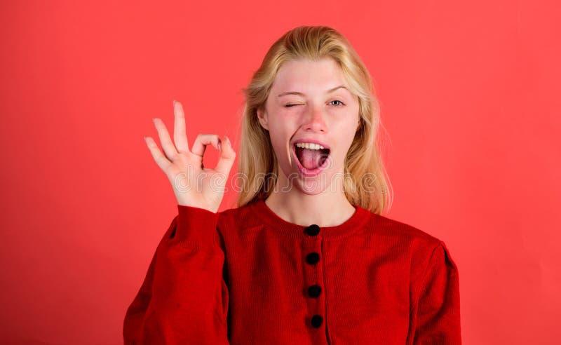 Lycklig framsida för flickablinkning medan ok gest för show över röd bakgrund Kvinna som tillfredsställs med allt Allt är ok elle royaltyfria foton