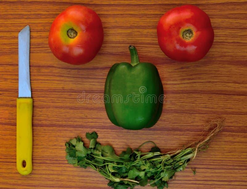 Lycklig framsida som utgöras av sunda grönsaker royaltyfria foton
