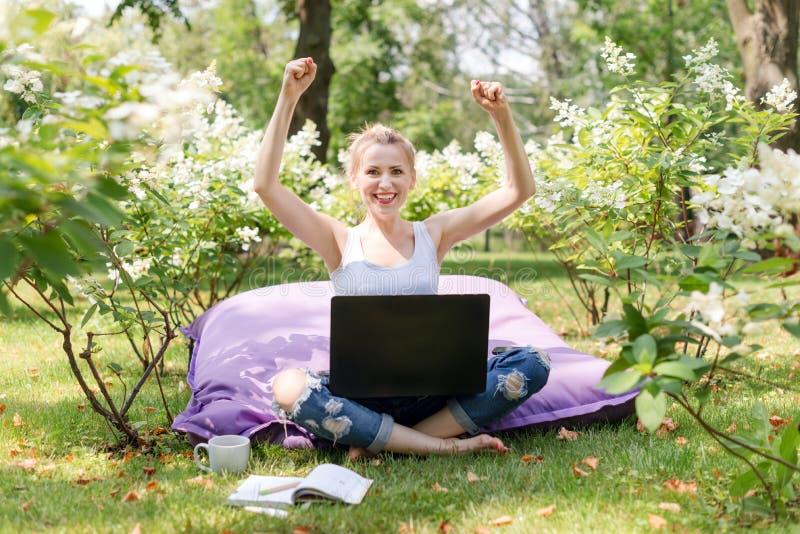 Lycklig freelancer som arbetar i trädgården Skriva och att surfa i internet Den unga kvinnan som kopplar av och har gyckel parker arkivbilder
