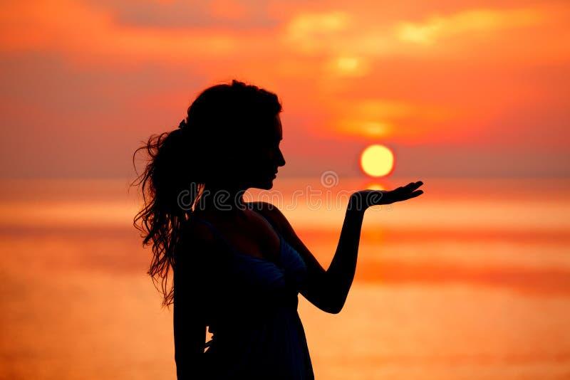 Lycklig fri kvinna som tycker om i havssolnedgång Silhouetted mot royaltyfri bild