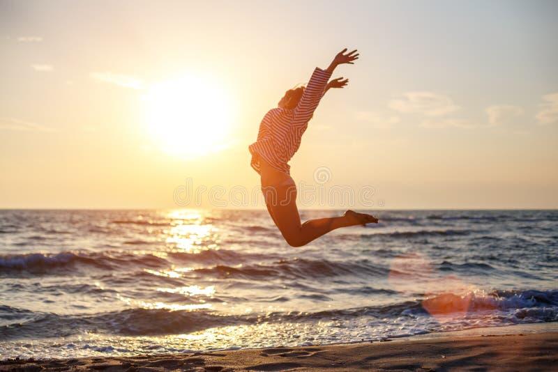 Lycklig fri kvinnabanhoppning med lycka på stranden i solnedgångsolen royaltyfria bilder