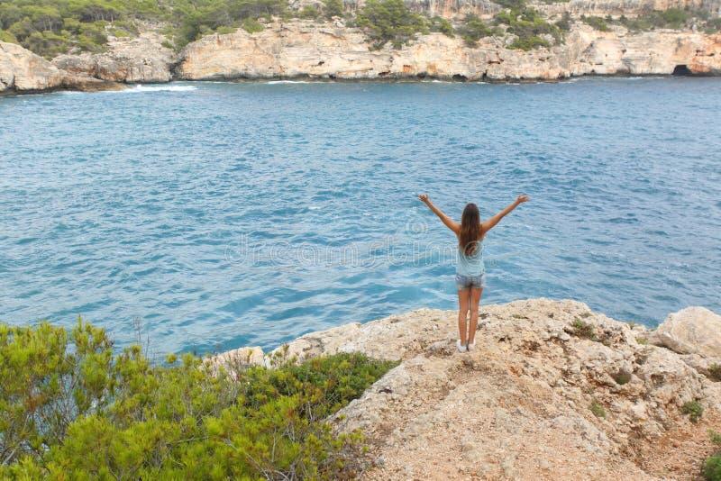 Lycklig fri tonåring som lyfter armar på semestrar arkivbild