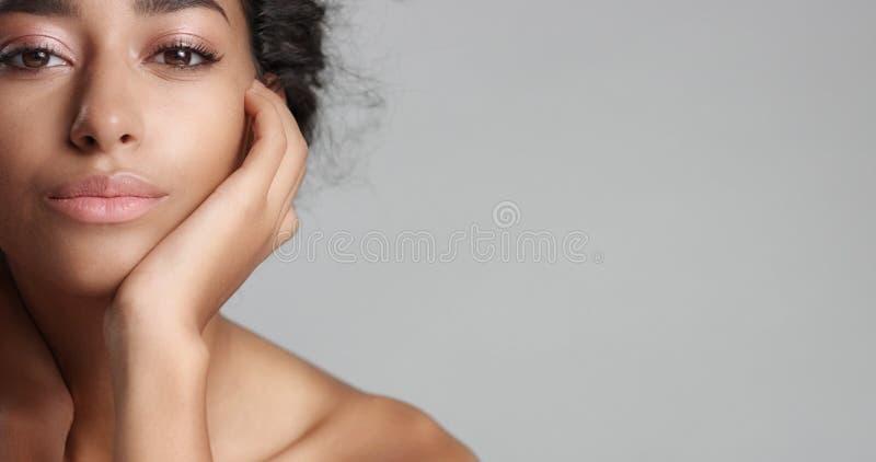 Lycklig fridfull ung kvinna med härliga olivgröna för hud och ideala hud- och bruntögon för lockigt hår i studio fotografering för bildbyråer