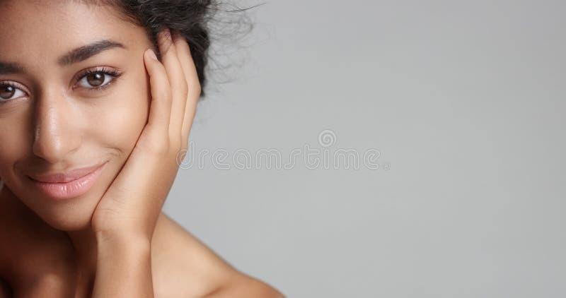 Lycklig fridfull ung kvinna med härliga olivgröna för hud och ideala hud- och bruntögon för lockigt hår i studio royaltyfri foto