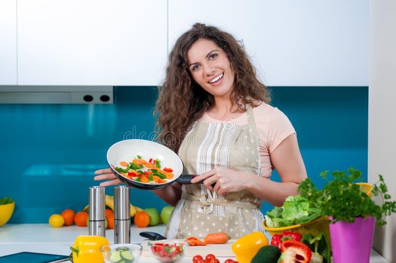 Lycklig fru som lagar mat sund mat arkivbilder