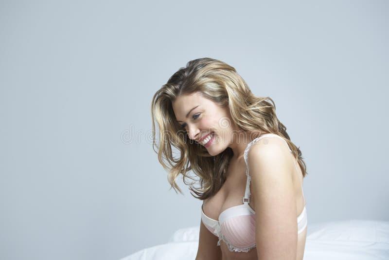 Lycklig fundersam kvinna i säng arkivbilder