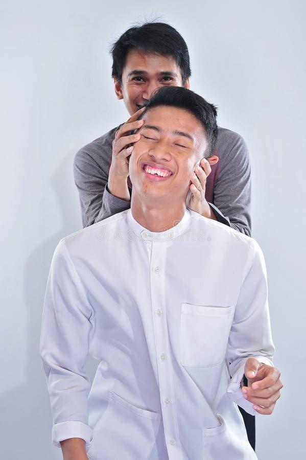 Lycklig galen photoshot med hans brorsoner, medan fasta på ramadan kareem i liten studio royaltyfria foton
