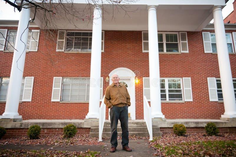 Lycklig gamal man framme av hans hus royaltyfria foton