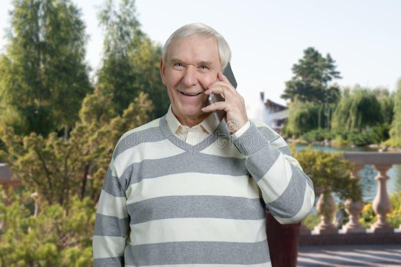 Lycklig gamal man som talar på den utomhus- telefonen arkivfoto
