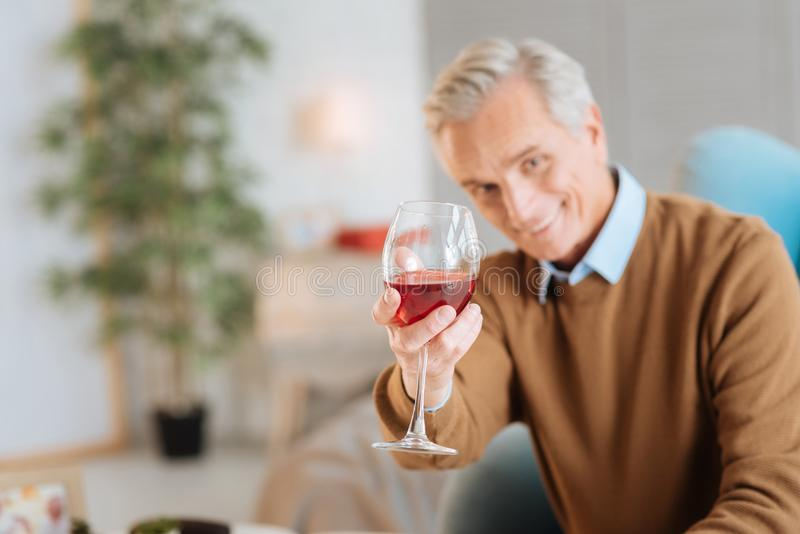 Lycklig gamal man som tycker om hans exponeringsglas av rött vin royaltyfria foton
