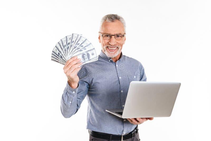 Lycklig gamal man som visar dollar i hand och ler till kameran royaltyfri bild