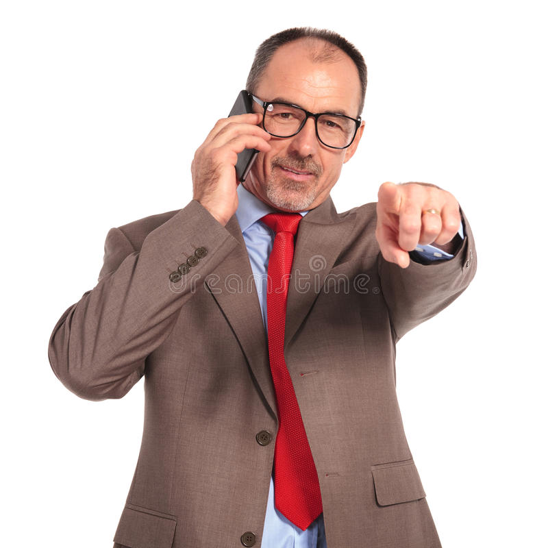 Lycklig gammal affärsman som talar på telefonen och pekar fingret royaltyfri bild