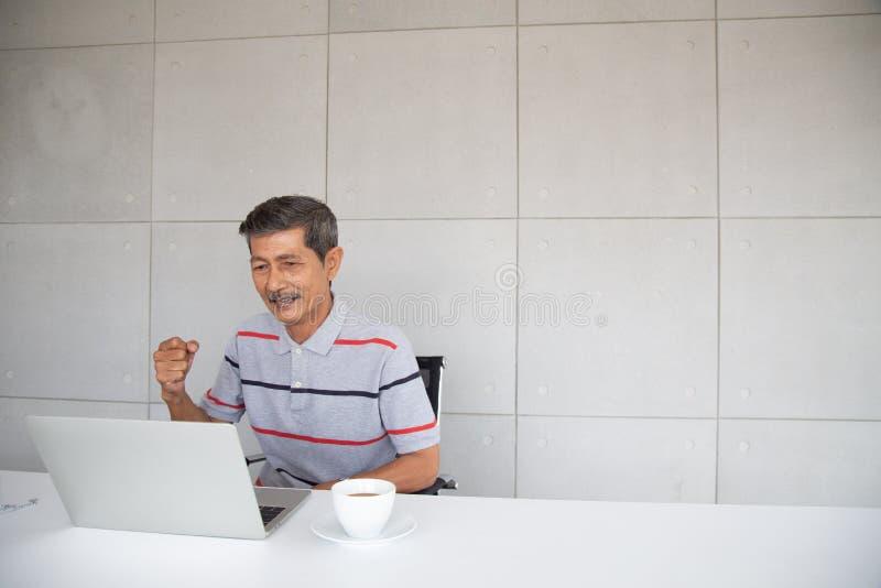 Lycklig gammal asiatisk man och leende med hans framgång royaltyfri foto