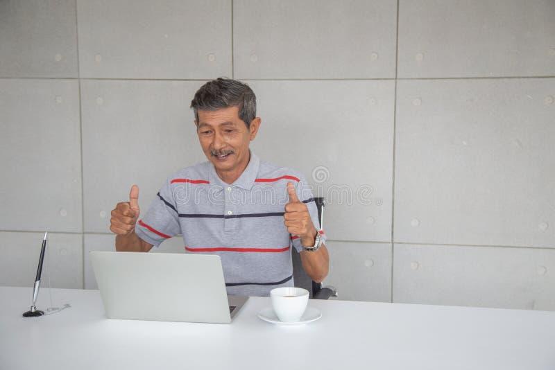 Lycklig gammal asiatisk man och leende med hans framg?ng royaltyfri fotografi
