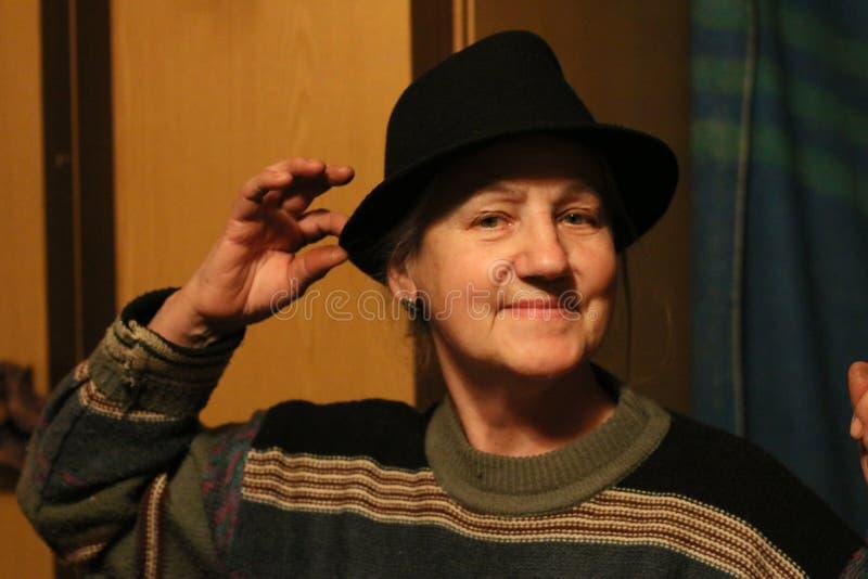 Lycklig gammal dam i svart hatt i skymning royaltyfri fotografi