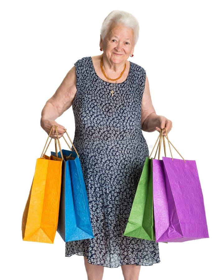 Lycklig gammal kvinna med shoppingpåsar royaltyfri fotografi