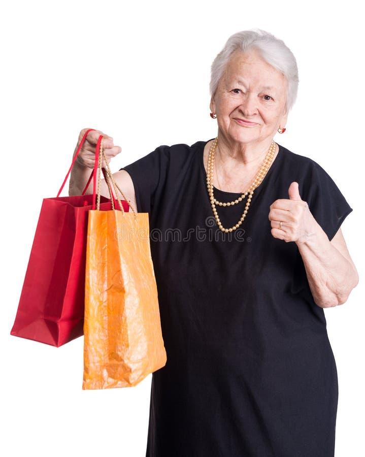 Lycklig gammal kvinna med shoppingpåsar fotografering för bildbyråer